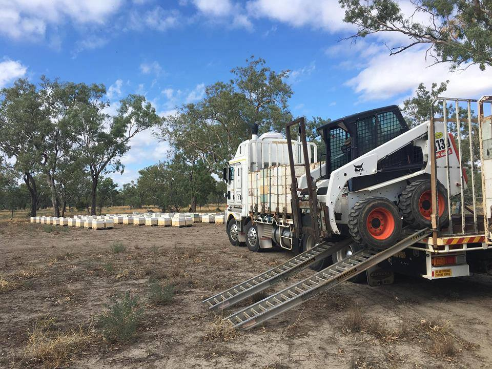 excavator is loaded on a truck with hives